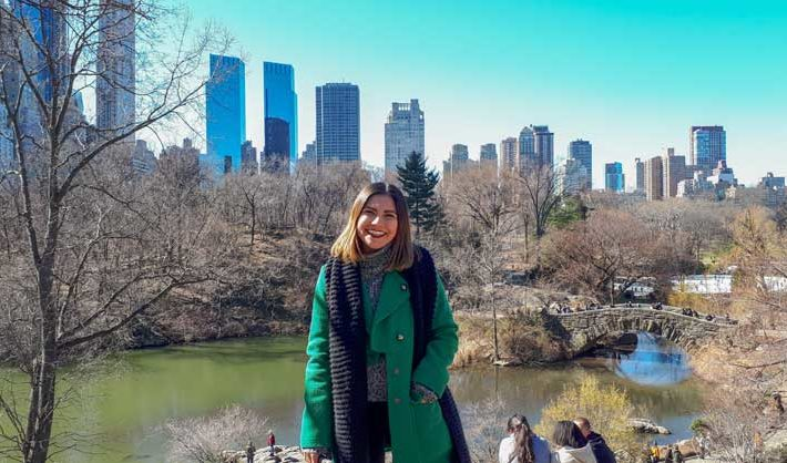 Young woman stands in Central Park in Manhattan in front of a pond and buildings