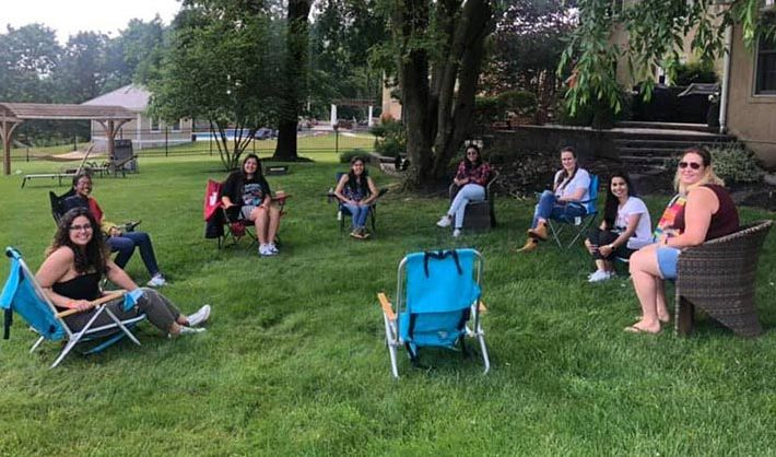 Several au pairs and their local coordinator sit on folding chairs outside while social distancing