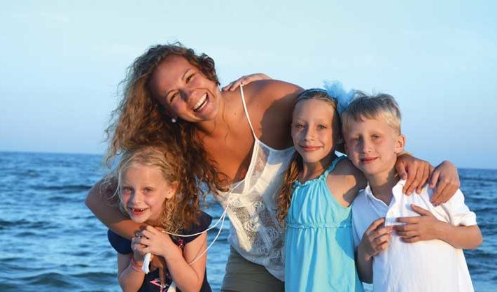 Young woman stands on beach hugging three school-age children