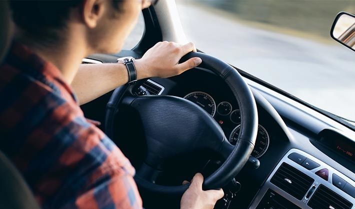 Young woman in car with hands on steering wheel