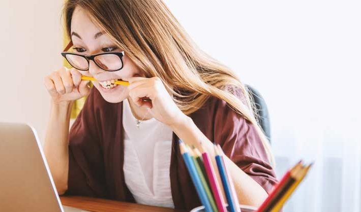 Woman in glasses bites pencil while looking at laptop
