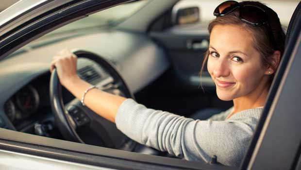 A smiling young woman in a car with a hand on the steering wheel