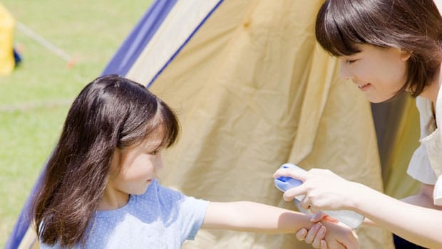 Child with carer applying insect repellent.