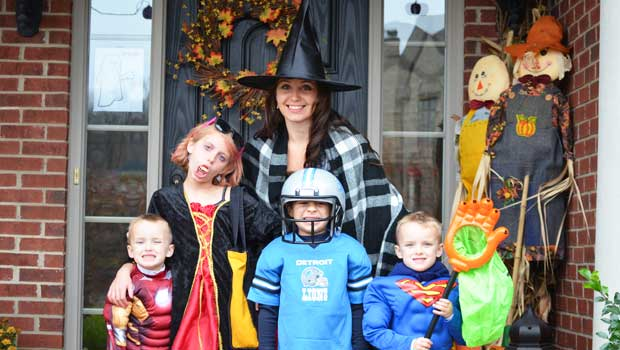 au pair, dressed as witch, with children in Halloween costumes