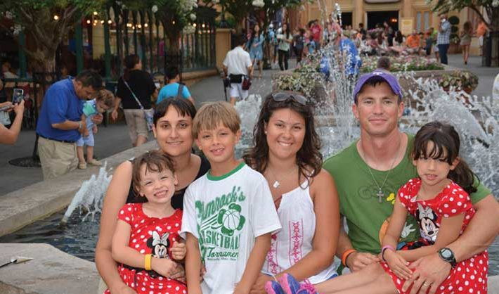 A father, mother, au pair, and three kids sit on a fountain