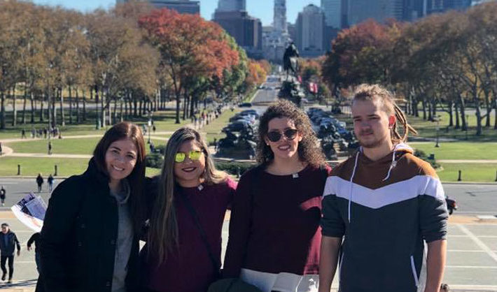 A young man and three young women standing in front of a park