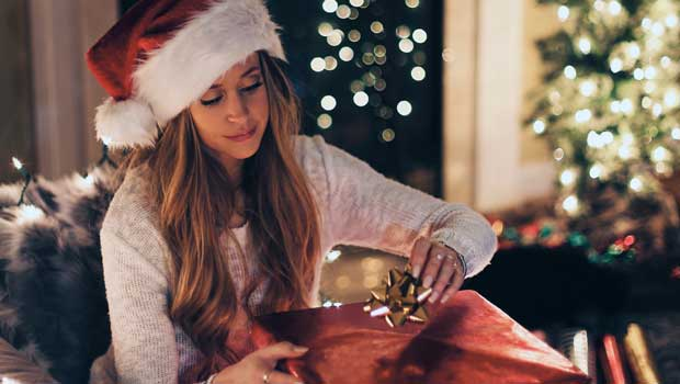 A woman in a Santa hat opens a Christmas present
