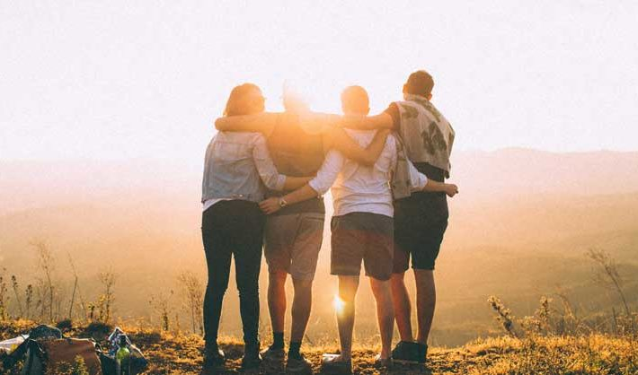 Four people hugging in a field
