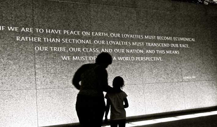 Silhouette of adult and child on Martin Luther King memorial wall in Washington DC