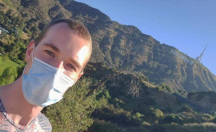 man in mask in front of Hollywood sign