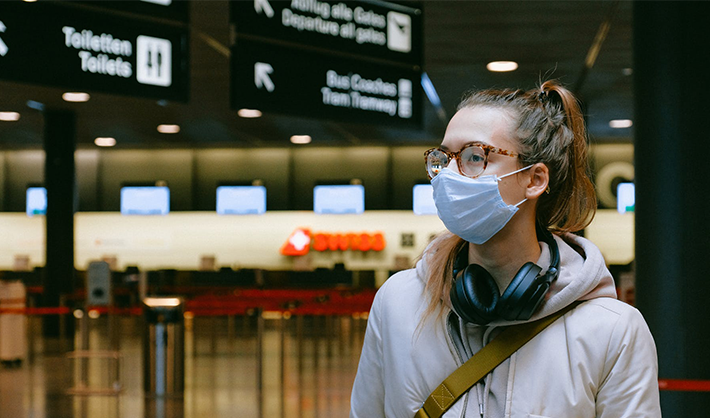 Young woman in face mask at airport.