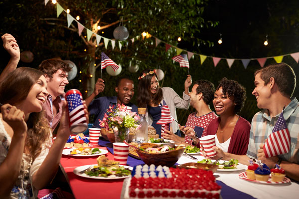 People seated at a table with U.S. flags and red, white, and blue food and cups.