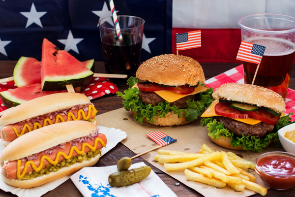 A table with U.S. flags and a red, white, and blue theme, along with hotdogs and hamburgers.