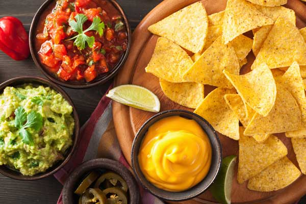 A table with chips, salsa, nacho dip, and guacamole dip.
