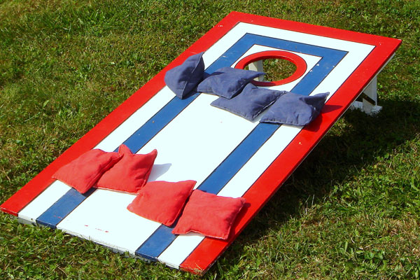 A cornhole board with red, white, and blue paint.