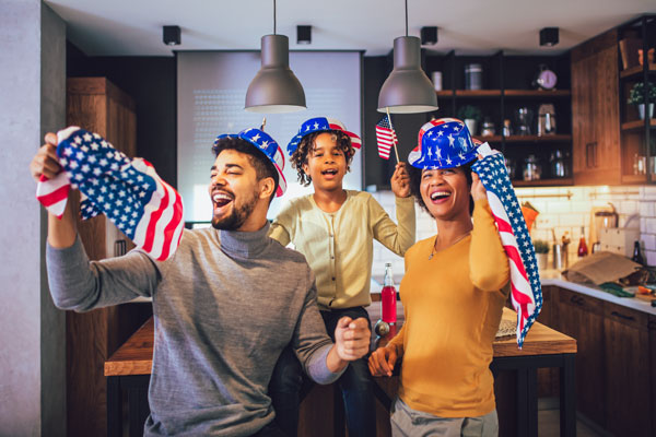 Three people with U.S. flags and red, white, and blue hats stand in a kitchen.
