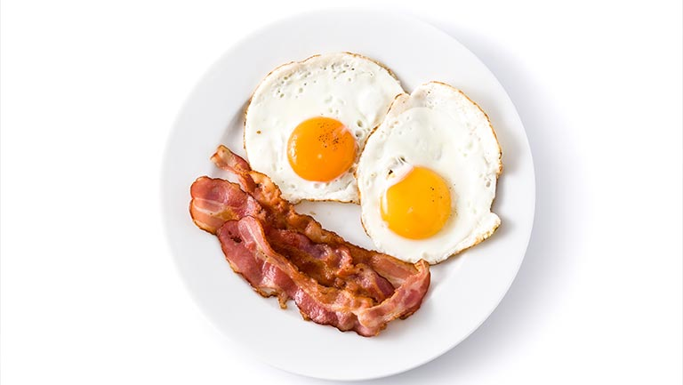 A plate of bacon and sunny-side-up eggs.