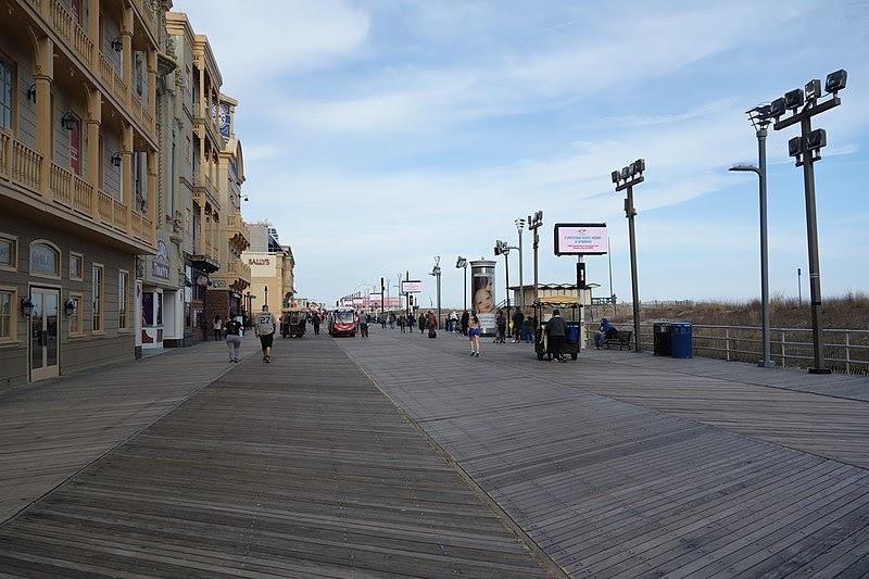 People walk along a beach boardwalk.
