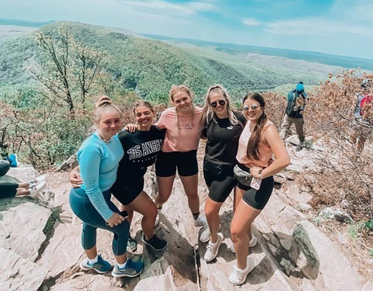 Five woman smile on a mountaintop.