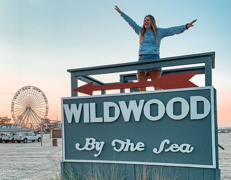 A smiling woman stands on a beach sign with a ferris wheel in the background.