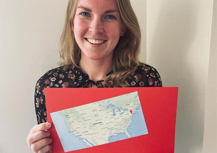 A woman holding a poster-board with a map of the United States and the name of a New Jersey city.