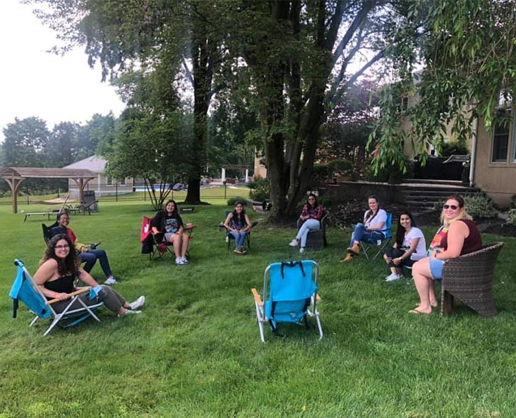 Eight au pairs sit socially-distanced in a circle in a backyard.