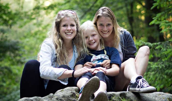 Mother, daughter, and au pair smile while sitting on a rock in the forest