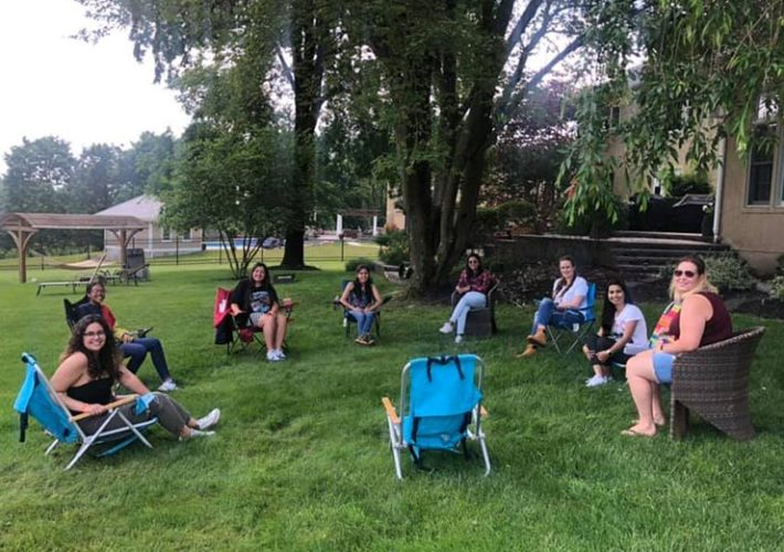 A group of au pairs practice social distancing outdoors during their monthly meeting.