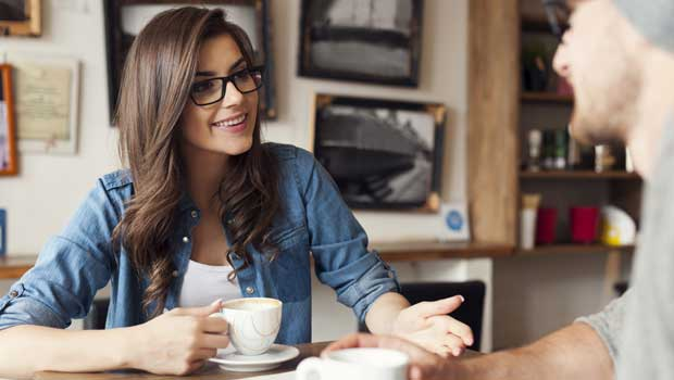 Young woman speaks to man while both drink coffe