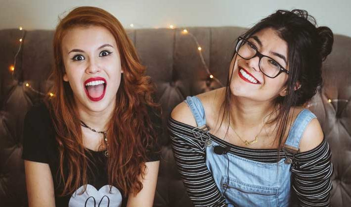 Two young women laugh together while sitting on sofa