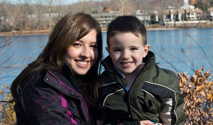 Au pair with toddler in front of lake