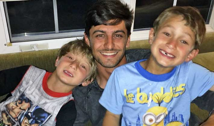 Male au pair with two host kids on couch