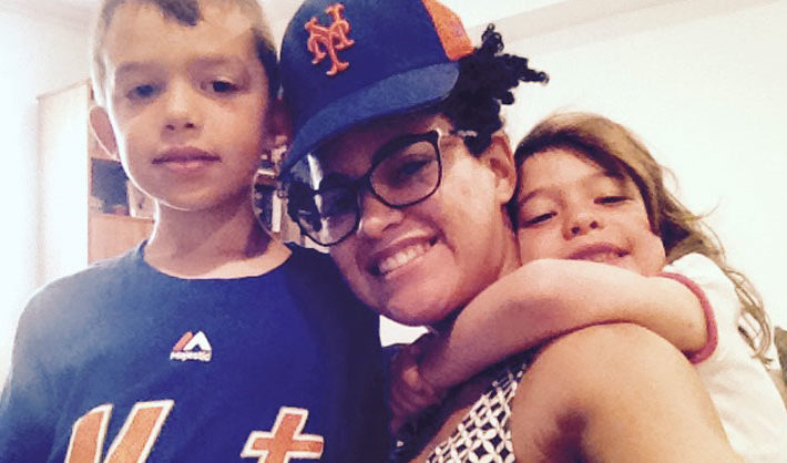Au pair wearing baseball cap with two children