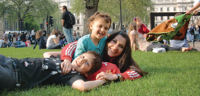 au pair lying in park with host kids