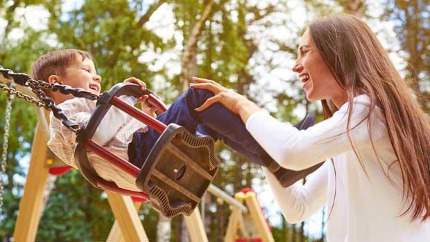 Au pair swinging with child