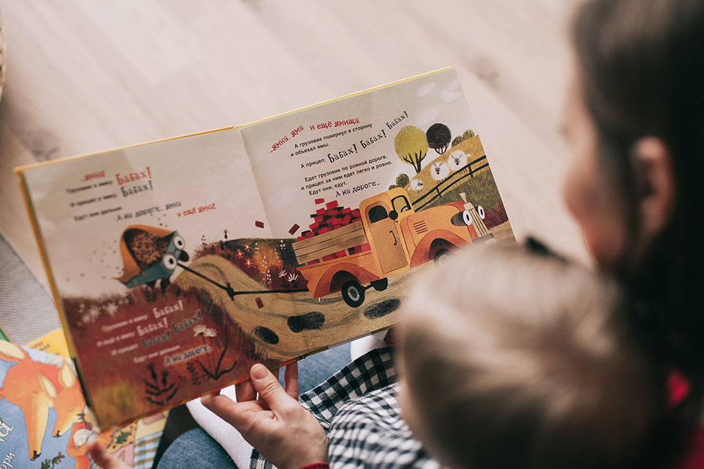 Au pair reads foreign language story book to host child.