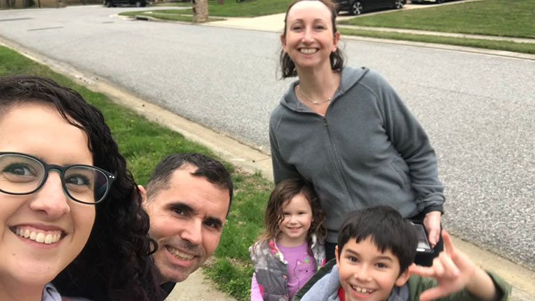 Au pair and host family stand on the sidewalk smiling.