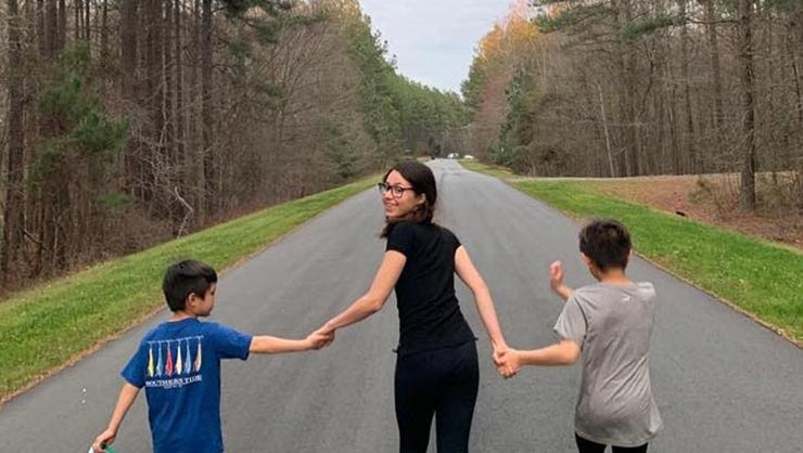 A young woman holds hands with two boys on a road surrounded by trees.